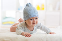 Baby boy lying on a children`s rug in blue cap. Royalty Free Stock Photography