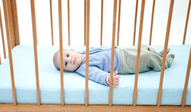 Baby boy lying in a cot Royalty Free Stock Photos