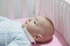 Baby boy lying in cot with bumper pad Stock Images