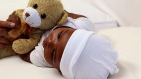Baby boy lying in crib with teddy bear stock footage