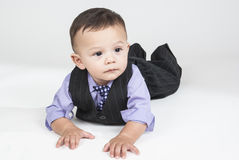 Baby boy lying down on the white floor. In the center of this horizontal image a small child lying down on the white floor with white background. He dressed up Stock Photos