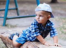 Baby boy lying on a log Royalty Free Stock Image