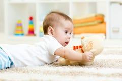 Baby boy lying with plush toy. Funny baby boy lying with plush toy stock photo