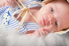 Baby boy lying on side in furry basket Royalty Free Stock Images