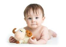 Baby boy lying on tummy with lamb toy. Baby boy lying on his tummy with lamb toy royalty free stock photos