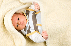 Baby boy is lying under blanket royalty free stock image