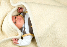 Baby boy is lying under blanket royalty free stock photo