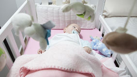 Baby boy lying in white cot with mobile Stock Image