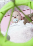 Baby boy lying in white cot with mobile Royalty Free Stock Image