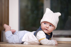 Baby boy lying in a white knitted cap Royalty Free Stock Images
