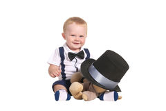 Baby boy magician hiding soft toy under cylinder. Baby boy gentleman magician smiling and hiding soft toy under his black cylinder hat with silver ribbon stock images