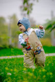 Baby boy making first steps. Baby boy in action on green grass in spring royalty free stock image