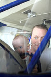 Baby boy and man smiling through windshield of airplane Stock Photo