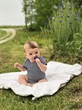 Baby boy sitting up on blanket smelling flower Stock Photography