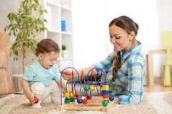 Baby boy and mom play with educational toy indoor. Baby boy and mom play with educational toy in nursery at home royalty free stock photography