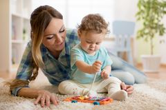Baby boy and mom playing in white sunny bedroom. Kids with educational toy in nursery. Royalty Free Stock Photos