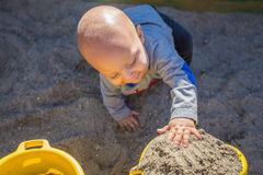 Baby boy 10-12 months old playing in sandbox. Royalty Free Stock Images