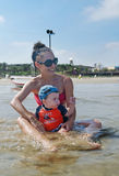Baby boy and mother at the beach. Cute Baby boy and mother in the ocean royalty free stock images