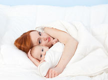 Baby boy with mother in bed Stock Photo