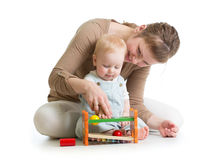 Baby boy and mother playing together with logical toy stock photos