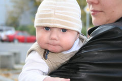 Baby boy in mother's arms. A view of a little baby boy wearing a knit hat on a chilly day, being held in his mother's arms royalty free stock photography
