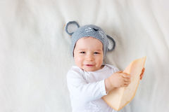 Baby boy in mouse hat lying on blanket with cheese Stock Photography