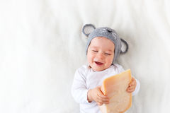 Baby boy in mouse hat lying on blanket with cheese Stock Images