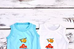 Baby boy new cartoon t-shirts. Toddler boy collection of round neck sleeveless t-shirts on white wooden background, top view. Infant boy summer clothes and Stock Photography