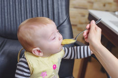 Baby Boy on Office Chair Eating Porridge Royalty Free Stock Image