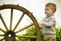 Baby boy with old wooden wheel Royalty Free Stock Photography