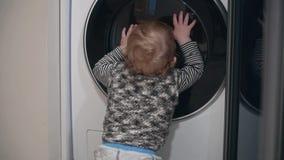 Baby boy one year old boy looking washing machine at home. Baby boy closes the washing machine stock video