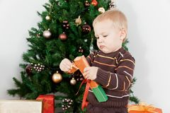 Baby boy opening the christmas-box Stock Photos