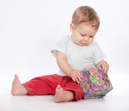 Baby boy opening gift box on white Stock Photos