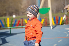Baby boy in orange jaket and blue jeans Stock Photos