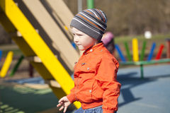 Baby boy in orange jaket and blue jeans Royalty Free Stock Images