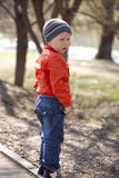 Baby boy in orange jaket and blue jeans Royalty Free Stock Photos