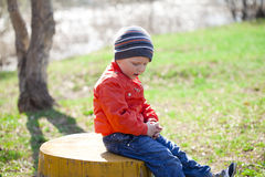 Baby boy in orange jaket and blue jeans Stock Image