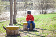 Baby boy in orange jaket and blue jeans. Little boy sitting on a stump in the spring park. Baby boy in orange jaket and blue jeans, outdoors Royalty Free Stock Image