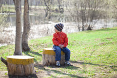 Baby boy in orange jaket and blue jeans. Little boy sitting on a stump in the spring park. Baby boy in orange jaket and blue jeans, outdoors Stock Image
