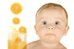 Baby boy with orange juice Royalty Free Stock Image