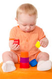 Baby boy in orange playing with toy pyramid Stock Photos
