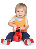 Baby boy in orange, sitting with red boxing gloves. Stock Photos