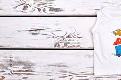 Baby boy organic cartoon t-shirt. Toddler boy white cotton transport illustration t-shirt  on white wooden background, copy space Royalty Free Stock Photo