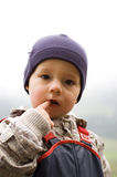 Baby Boy Outdoors. Cute baby boy with blue beanie with his finger in his mouth Stock Photo