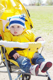 Baby boy outdoors on yellow buggy in spring Stock Photos