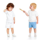 Baby boy with paint brush and girl standing full length isolated. On white background royalty free stock photography