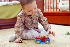 Baby boy with painted mustache playing toy car. Baby boy with funny painted mustache playing toy car. home interior Stock Images