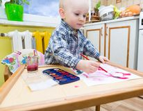 Baby boy painting with watercolors Stock Photos