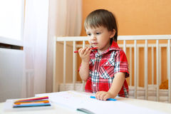 Baby boy painting with wax pencils Royalty Free Stock Image