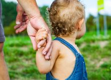 Baby Boy in park. trust family hands of child son and father. On field nature outdoor stock images
